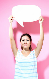 Young woman holding a speech bubble on a pink background