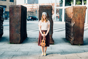 Young woman holding an ukulele outdoor in the city, looking at camera, serious - musician, composer concept