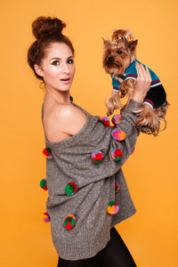 Young woman holding her cute terrier dog isolated on orange background