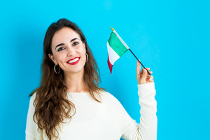 Young woman holding Italian flag on a blue background