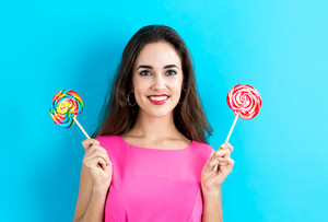 Young woman holding lollipops on a blue background