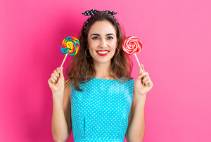 Young woman holding lollipops on a pink background