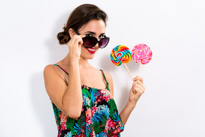Young woman holding lollipops on a white background