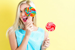 Young woman holding lollipops on a yellow background