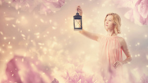 Young woman in a pink dress with a lamp in pink abstract flower background