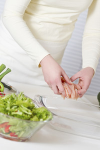 Young woman in a white kitchen making a chicken meat fillet dish. Vegetables.