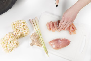 Young woman in a white kitchen making a chicken meat fillet dish with vegetables, ginger and pasta / noodles.