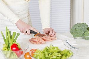 Young woman in a white kitchen making a chicken meat fillet dish.