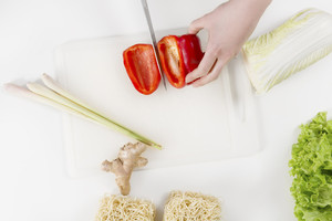 Young woman in a white kitchen making a healthy food with red pepper, vegetables, lime gras, ginger and pasta / noodles.