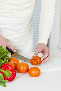 Young woman in a white kitchen making a healthy salad with vegetables. Cutting tomato with a knife.