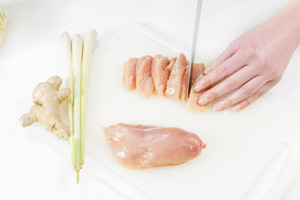 Young woman in a white kitchen making a wok with chicken meat fillet , vegetables, lime gras, ginger and pasta / noodles.