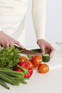 Young woman in a white kitchen making salad with vegetables. Cutting cucumber with a knife.