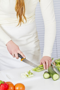 Young woman in a white kitchen making salad with vegetables. Cutting spring onion with a knife.