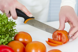 Young woman in a white kitchen making salad with vegetables. Cutting tomato with a knife.