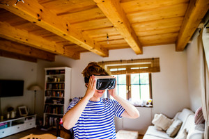 Young woman in blue striped t-shirt wearing virtual reality goggles standing in living room