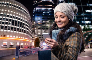Young woman in checked brown winter coat with smart phone outside in illuminated night city