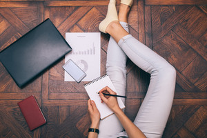 Young woman in jeans works at home and writes in a notebook, top view