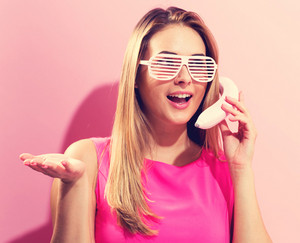 Young woman in pink with a funky banana and shutter shades