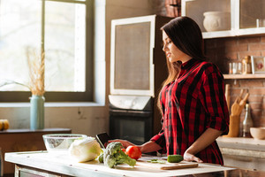 Young Woman in red shirt standing in kitchen with tablet computer and looking recipes. Side view