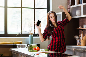 Young Woman in red shirt with eyes closed listening to music, dancing in kitchen with phone and headphone.