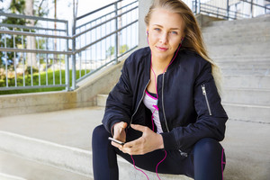 Young Woman In Sportswear Listening Music On Smartphone