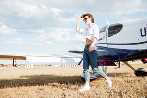 Young woman in sunglasses walking across the field with plane on the background
