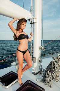 Young woman in swimsuit standing on yacht at sunny day and looking at sea