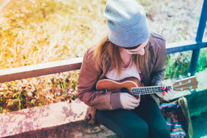 Young woman in the city playing ukulele - busker, musician, composer concept - filtered colorful