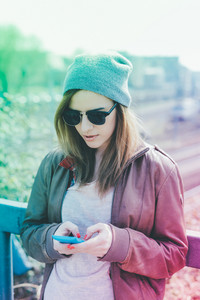 Young woman in the city using smart phone hand hold - technology, social network, phubbing concept - filtered colorful