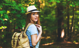 Young woman in the forest with a backpack and hat