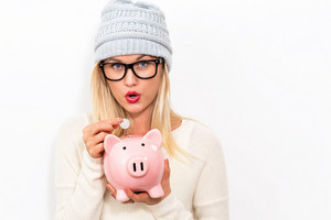 Young woman in winter clothes with a piggy bank