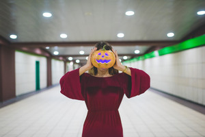 Young woman indoor with pumpkinf face - halloween concept