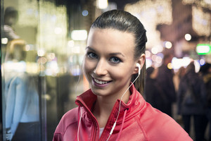 Young woman jogging at night in the city with headphones