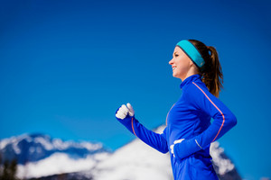 Young woman jogging outside in sunny winter mountains