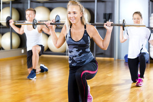 Young Woman Lifting Barbell Rod With Friends In Gym