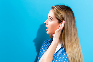Young woman listening on a blue background