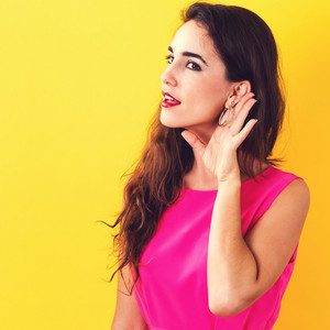 Young woman listening on a yellow background