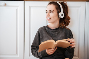Young woman listening to music with headphones and reading recipe book in the kitchen at home and looking away