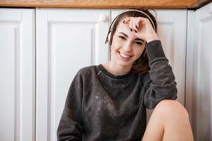 Young woman listening to music with headphones in the kitchen at home and looking at camera