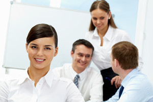 Young woman looking at camera and smiling against her communicating colleagues