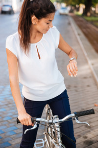 Young woman looking time on her wrist watch while sitting on the bicycle