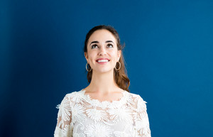 Young woman looking upward on a blue background