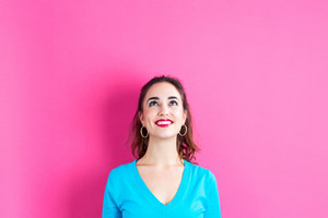 Young woman looking upward on a pink background