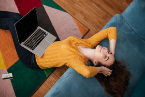Young woman lying on a couch and shopping online with credit card and laptop at home