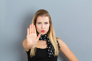 Young woman making a rejection pose on a gray background