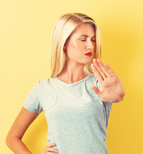 Young woman making a rejection pose on a yellow background
