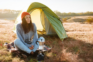 Young woman making coffee outdoors near a tent