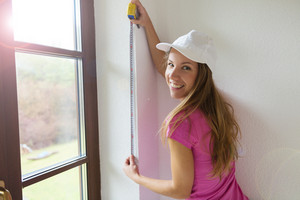 Young woman measuring the wall with tape measure