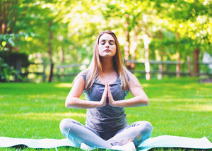 Young woman meditating outside on a beautiful summer day