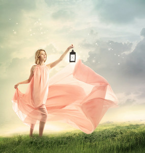 Young woman on a fantasy grassy hilltop with antique lamp